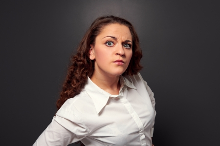 distrust: studio shot of curly woman looking at camera. picture over dark background Stock Photo