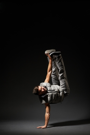 aerobica: stylish break dancer make the move. studio shot over dark background