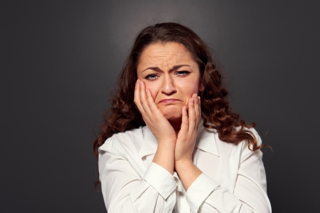 cabizbajo: mujer joven llorando. Imagen sobre fondo oscuro