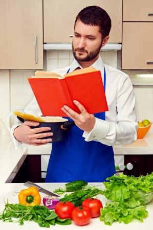attentively: handsome young man reading cookbook attentively at the kitchen