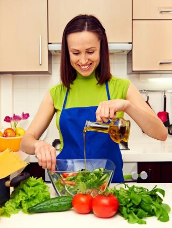 aceite de cocina: ama de casa feliz adición de aceite en la ensalada