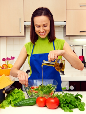 happy housewife adding oil in salad Stock Photo - 18205170