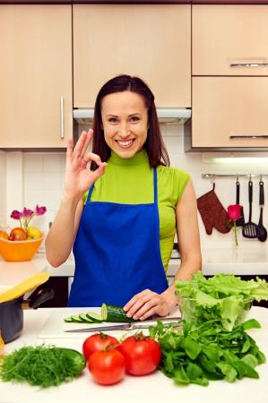 ama de casa: feliz ama de casa en el delantal azul que muestra el signo ok. un disparo en la cocina Foto de archivo
