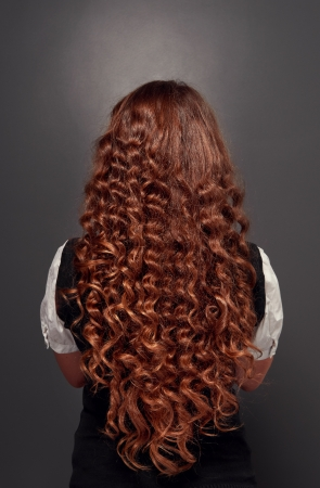 back view of beautiful natural brunette with long curly hair. studio shot over dark background  photo