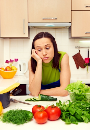 weary housewife standing in kitchen Stock Photo