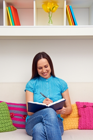 journals: smiley young woman sitting on sofa and keeping a journal