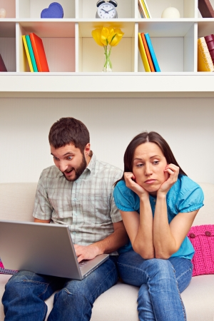 tedious: bored woman sitting while her boyfriend playing video game Stock Photo