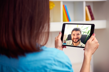 man and woman communicating through video chat on tablet pc photo