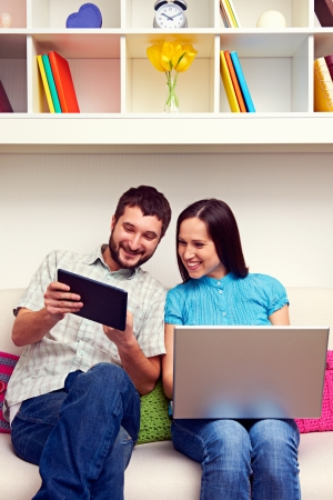 joyous: joyous man and woman looking at the tablet pc and smiling