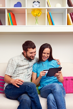 credit card purchase: smiley couple sitting on sofa and shopping on the internet  Stock Photo