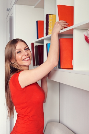 pretty woman getting a book and smiling Stock Photo - 18520134