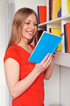 cheerful young woman reading the book and smiling Stock Photo - 18520130