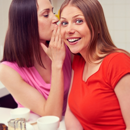 beautiful young woman whispering message to her friend photo