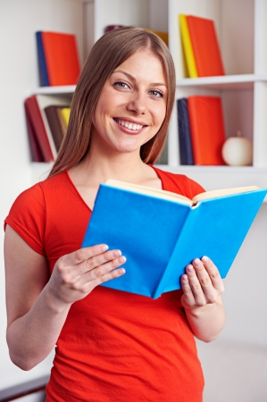 cheerful young woman holding the book and smiling photo