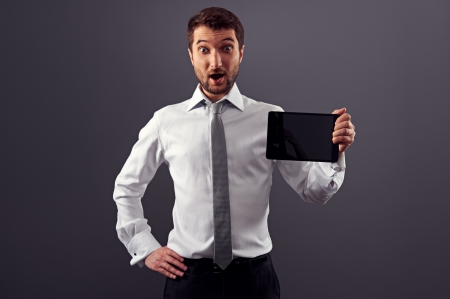 surprised man: amazed businessman showing the tablet pc. studio shot over grey background