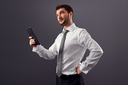 thoughtful businessman holding tablet pc and looking up photo