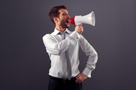handsome businessman using megaphone over dark background in studio Stock Photo - 18635378