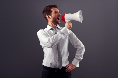 handsome businessman using megaphone over dark background in studio Stock Photo - 18635378