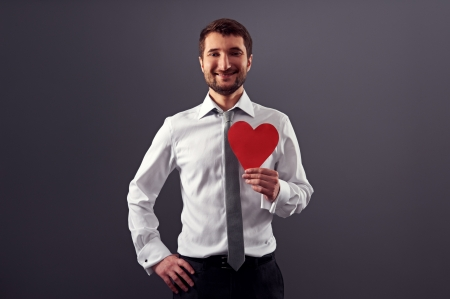 happy handsome man holding red heart and smiling. studio shot over dark background Stock Photo - 18635399