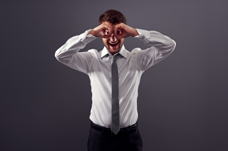 excited businessman looking through imaginary binocular. studio shot over dark background Stock Photo - 18635405