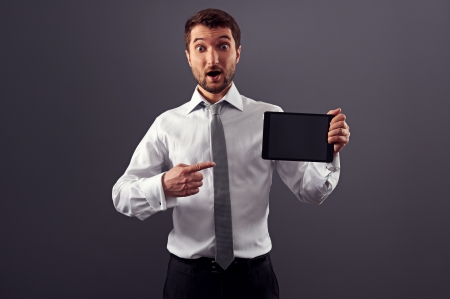 amazed man pointing at his tablet pc and looking at camera Stock Photo - 18635360
