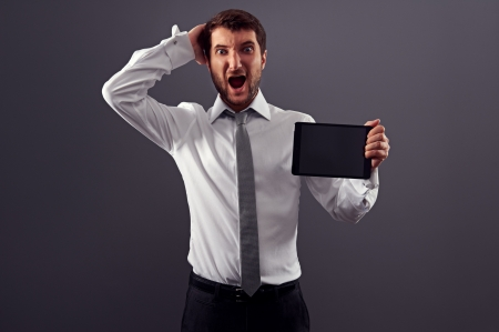 shocked man holding tablet pc and screaming. studio shot over dark background Stock Photo - 18635362