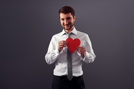 handsome smiley man holding red heart and looking at camera. studio shot over dark background Stock Photo - 18635401