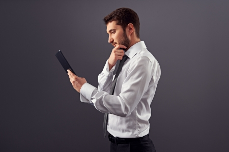 sideview portrait of thoughtful businessman with tablet pc. studio shot over dark background photo