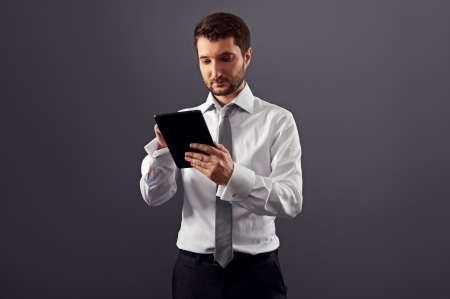 touch pad: young adult businessman working with tablet pc. studio shot over dark background