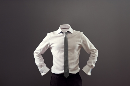 formal shirt: anonymous man in white shirt and black trousers over dark background