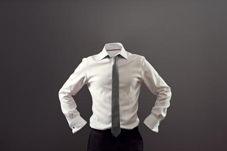 hombre anónimo con camisa blanca y pantalones negros sobre fondo oscuro