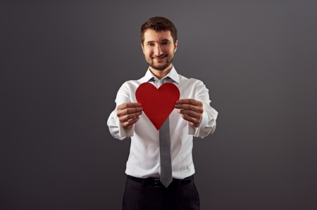 smiley handsome man showing red heart and looking at camera over dark background Stock Photo - 18767168