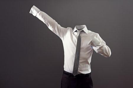 invisible man in formal wear standing like super man against grey background photo