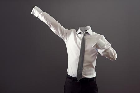 el hombre invisible en ropa formal de pie como super hombre contra el fondo gris