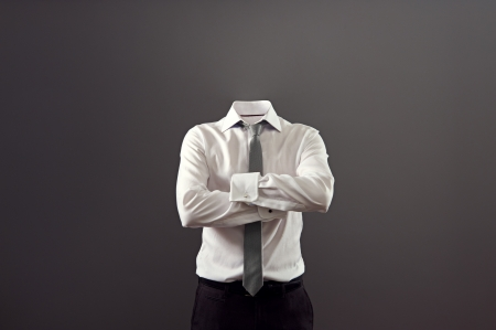 灰色の背景に対して彼の胸の上に腕を組んで立っている目に見えない男 写真素材