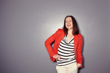 merriment: laughing brunette in red coat standing over dark background