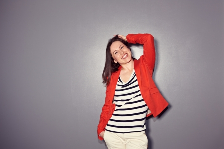 lively young woman is laughing over dark background Stock Photo