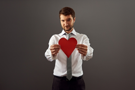 handsome man showing red heart over dark background Stock Photo - 18767170