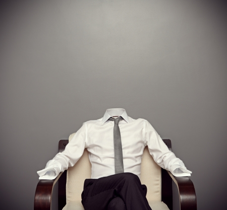 invisible: invisible man in formal wear sitting on armchair against grey background