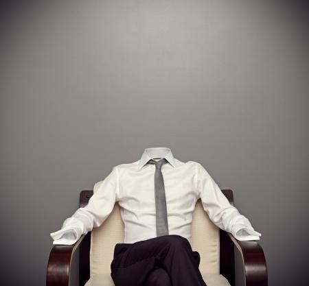 niewidoczny: Niewidzialny człowiek w wizytowym siedzi na fotelu, na szarym tle Zdjęcie Seryjne