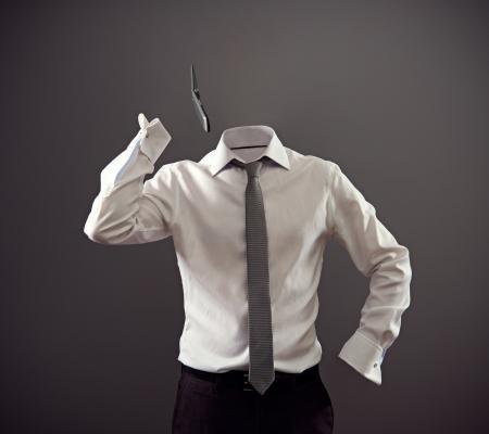 白いワイシャツおよび暗い背景の上に、携帯電話で話している黒いズボンで匿名の男