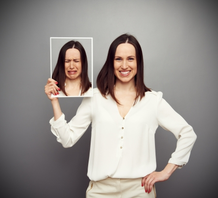 upset woman: young happy woman holding her sad picture Stock Photo