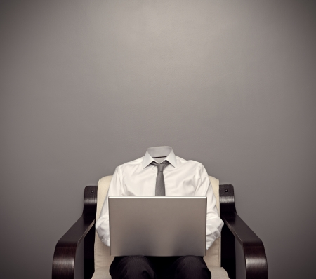 invisible: invisible man in formal wear sitting on chair and working with laptop against grey background