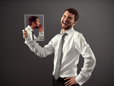 man in formal wear is laughing at a joke