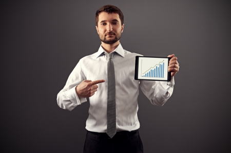 serious businessman holding tablet pc and pointing at growth chart photo