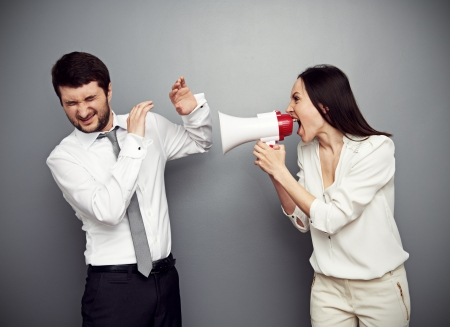 angry boss: angry woman shouting at the man over dark background