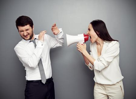 jefe enojado: mujer enojada gritando en el hombre sobre fondo oscuro