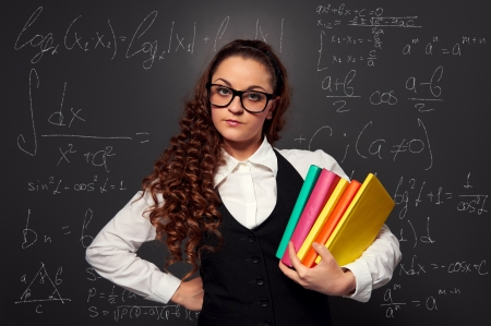 student in glasses with pile of books. picture over chalkboard photo