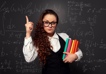 student in glasses with pile of books make attention sign. picture over blackboard photo