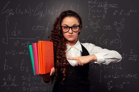 serious student in glasses pointing at pile of books. picture over blackboard photo